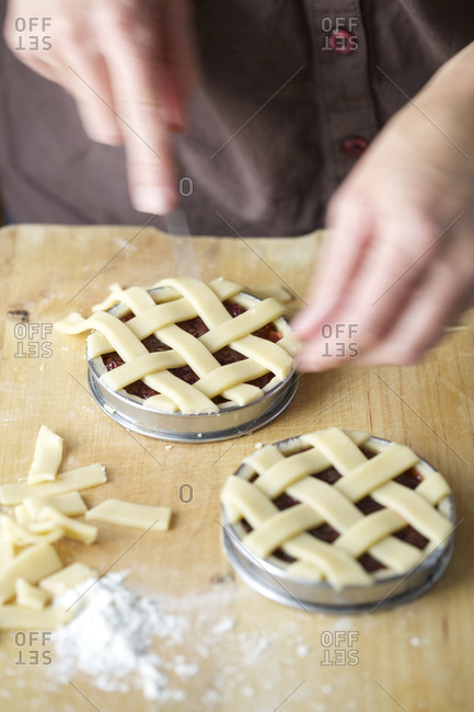 Person cutting off the excess pastry from lattice topped linzer tortes