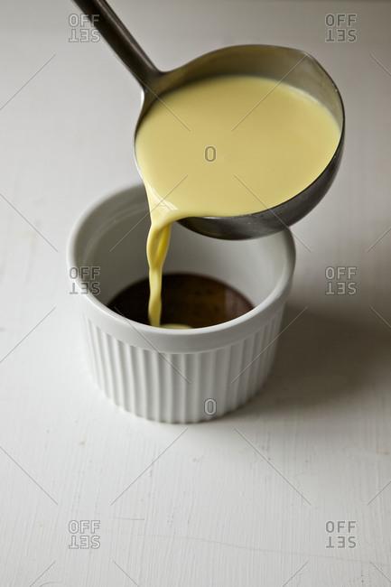 Pouring butternut mixture into a ramekin