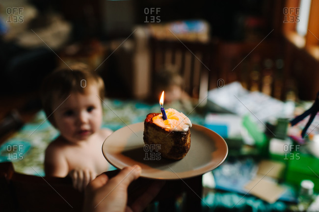 Person bringing a birthday cupcake for a baby