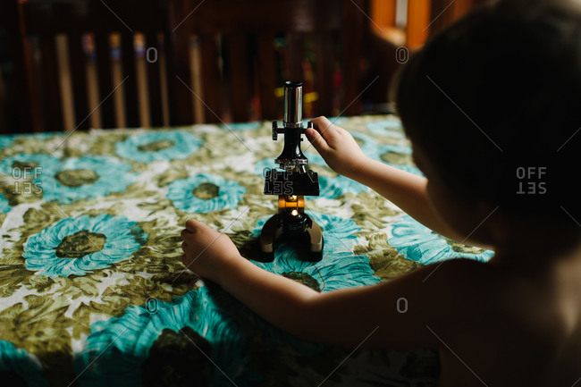 Boy playing with a microscope