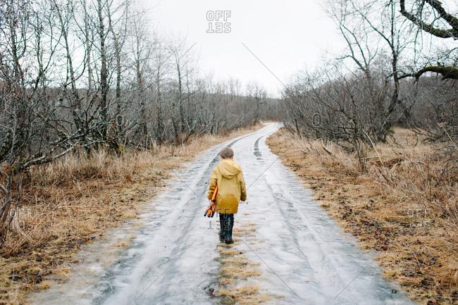 Boy walking on a wet road
