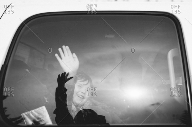 Boy waving inside a car