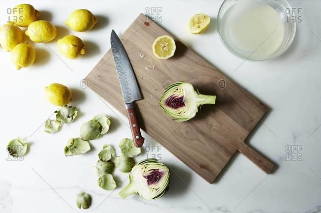 Still life of cut artichoke and lemons on cutting board