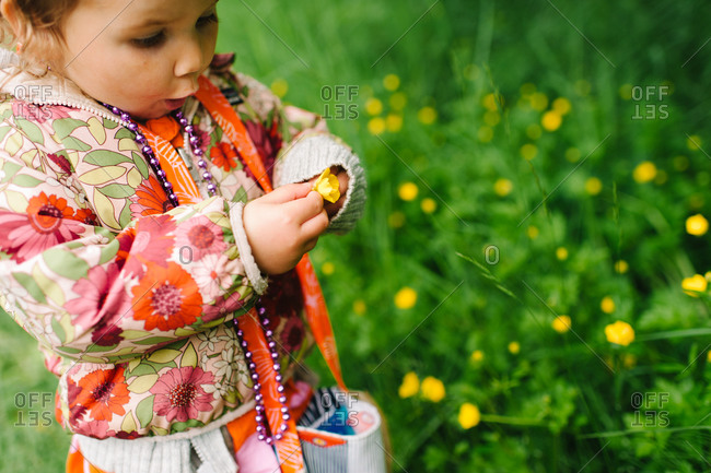 Little girl holding a yellow flower