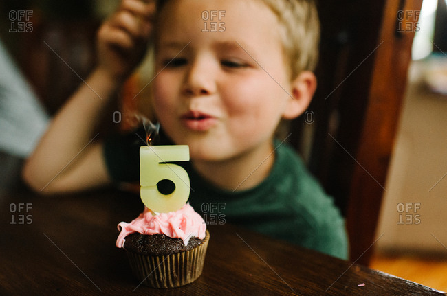 Boy blowing out birthday candle