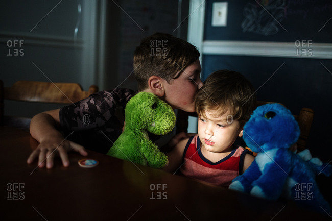 Older brother gives a kiss for his younger brother
