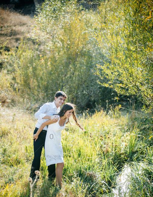 Newlyweds taking a walk in a meadow