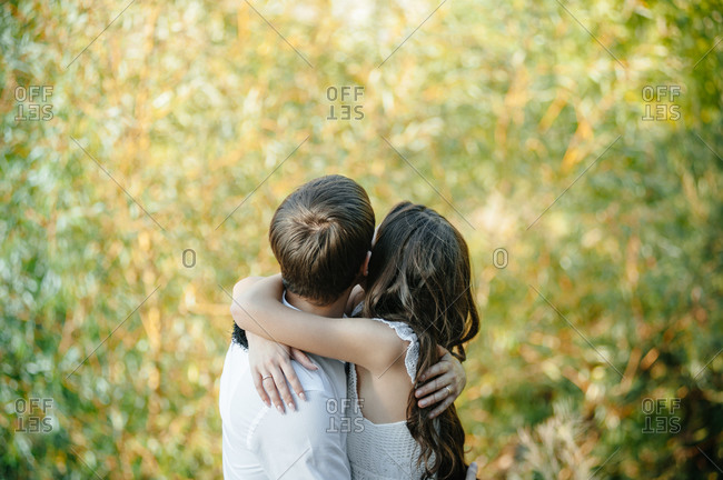 Newlywed couple hugging in a meadow