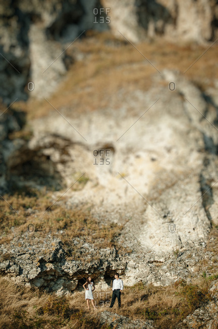 Newlyweds posing by a rock
