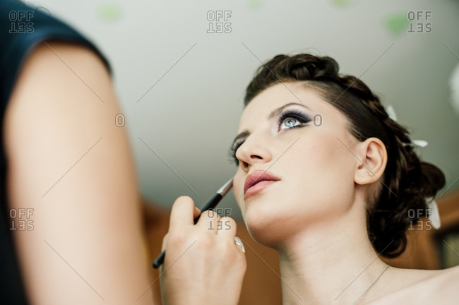 Woman applying make up on bride