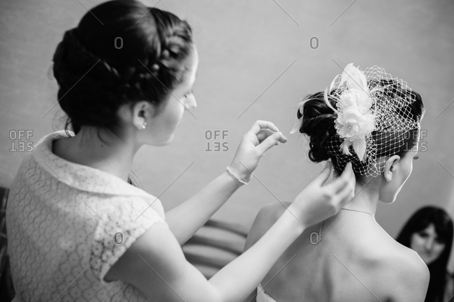 Woman adjusting bride's hair