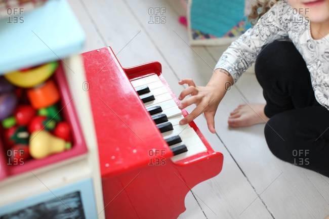 Girl's hand playing toy piano at playroom