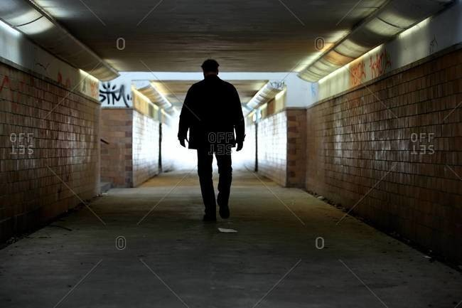 Rear view of criminal walking in subway
