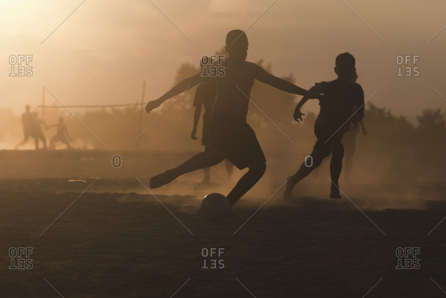Silhouette of boys play football on a dusty field, Vientiane, Laos