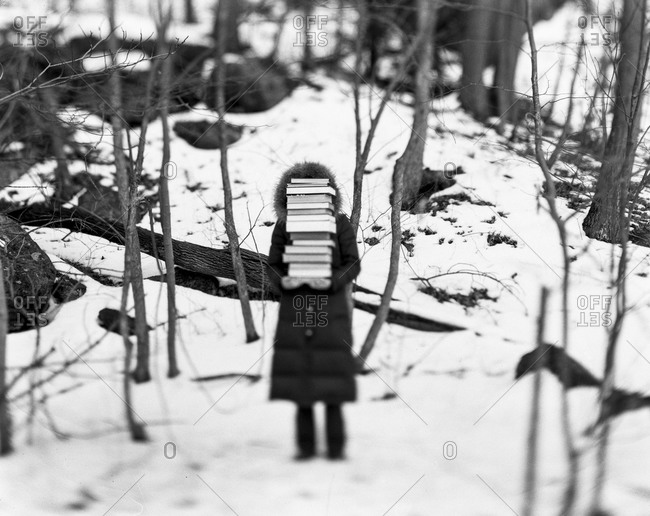 Woman carrying a stack of books in a snowy forest in New England, USA