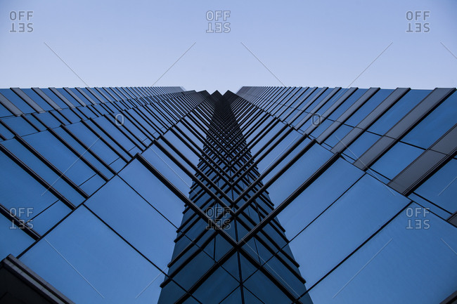 A glass fronted building reflecting the sky in Hong Kong