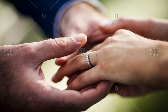 A husband puts a ring on his wife's finger during a wedding ceremony in Koh Samui, Thailand
