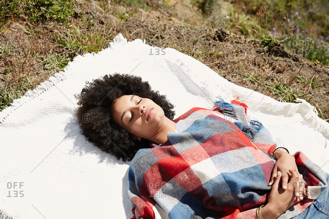Woman covered in poncho resting on picnic blanket