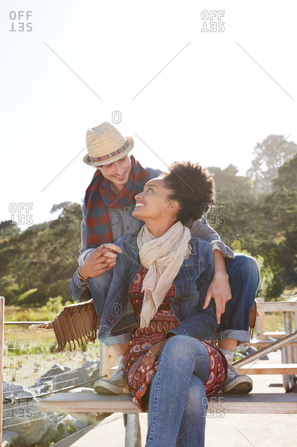Interracial couple sitting at picnic area in the nature