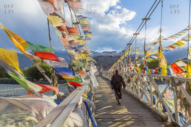 Rear view of man crossing bridge covered in prayer flags, Stakna monastery, near Leh, Ladakh, India