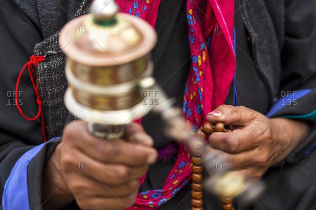 Close up of a Ladakhi woman holding prayer beads and prayer wheel