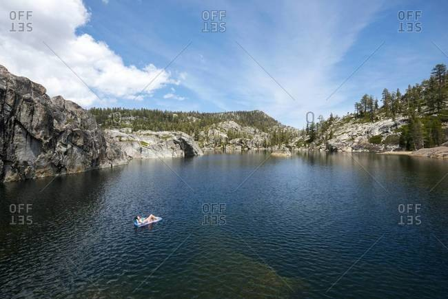 Woman floating on an inflatable raft on an alpine lake in Desolation Wilderness, California