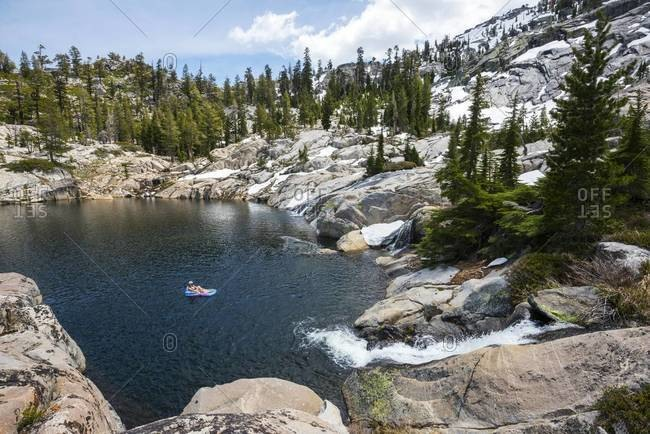 Woman floating on an inflatable raft on a pristine alpine lake with in Desolation Wilderness, California