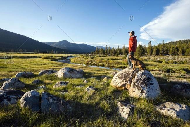 Man standing on a granite boulder with his dog with the Sierra Nevada mountains and the West Fork of the Carson River in the background in Hope Valley, California