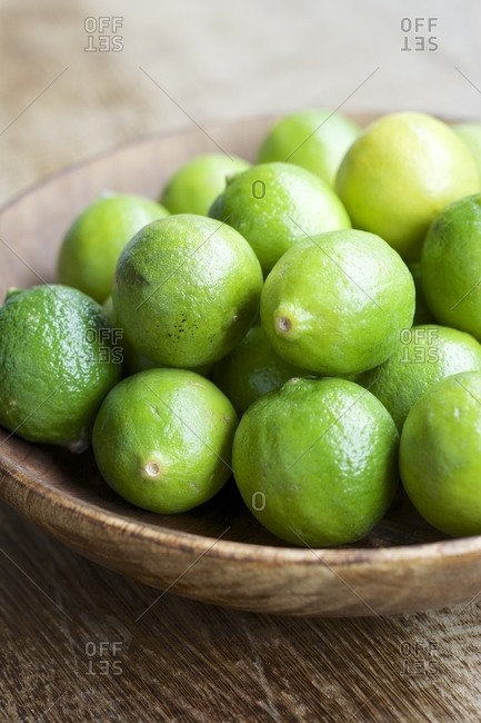 Key limes, Citrus aurantiifolia, in a wooden bowl