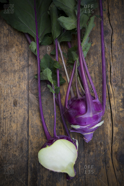Whole and a half blue turnip cabbages, Brassica oleracea var. gongylodes L. on dark wood, elevated view