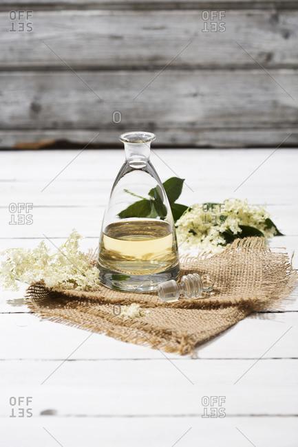 Glass bottle of home-made elderflower syrup and elderflowers, Sambucus, on jute