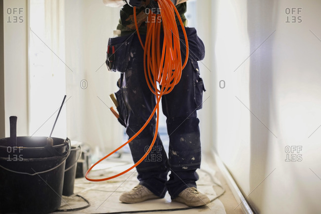 Low section of male carpenter holding wire cables at site