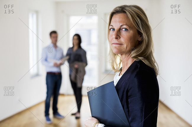 Real estate agent with couple standing in background at home