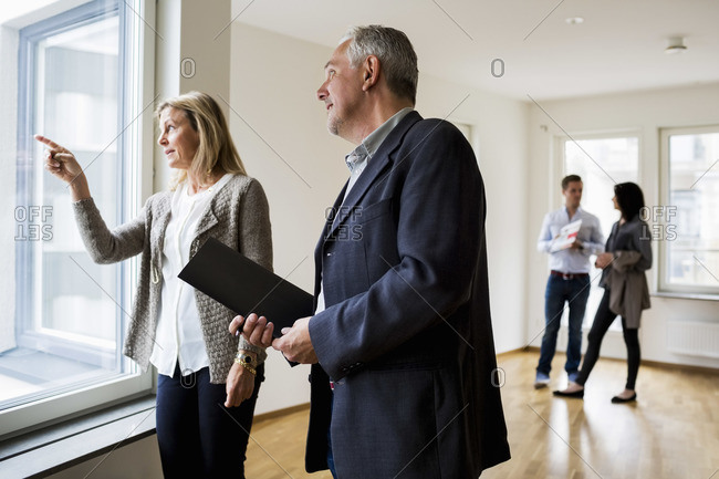 Real estate agents discussing while couple standing in background at new home