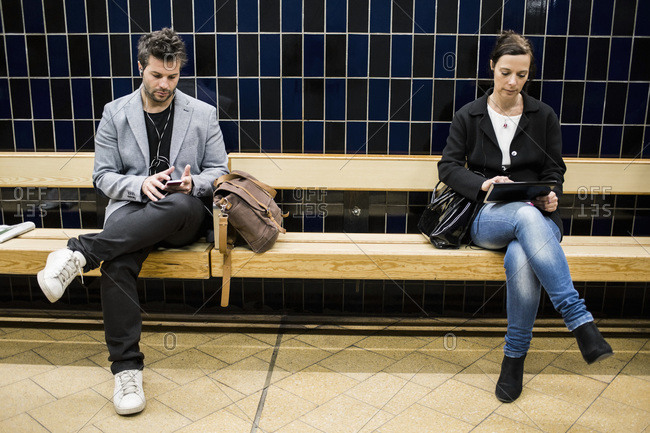 People using technologies on bench at subway station