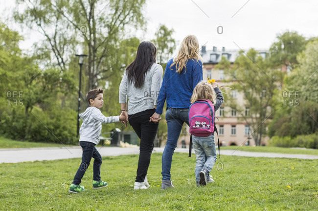 Rear view of female homosexual family walking in park