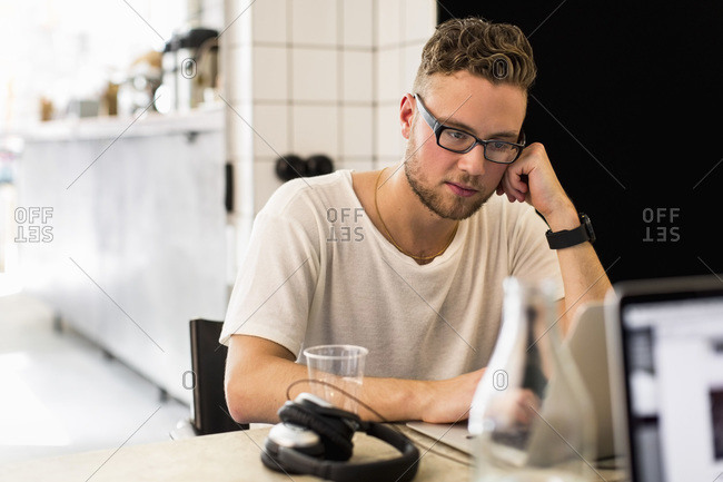 Thoughtful young businessman working in creative office