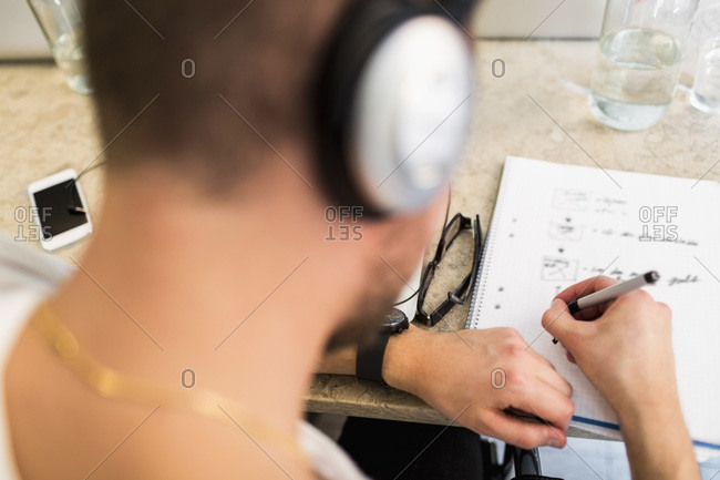 Rear view of young businessman writing in book at office desk