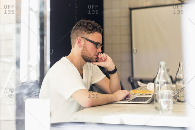 Side view of young businessman using laptop in creative office