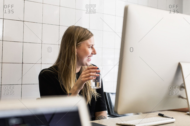 Smiling young businesswoman having glass of water in new office