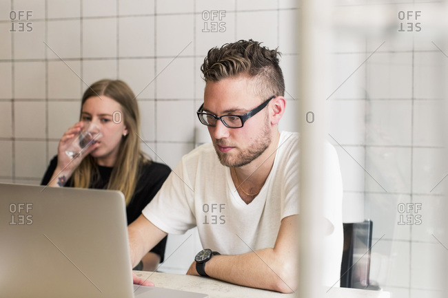 Young businessman working on laptop with female colleague having glass of water in new office