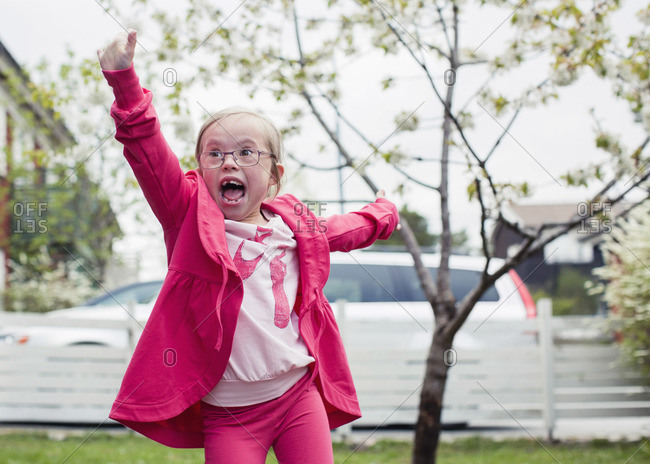 Excited girl with arms outstretched enjoying in lawn