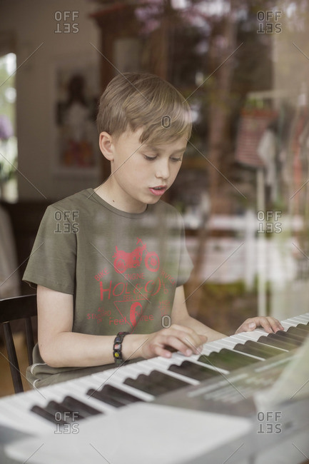 Boy singing while playing piano in house