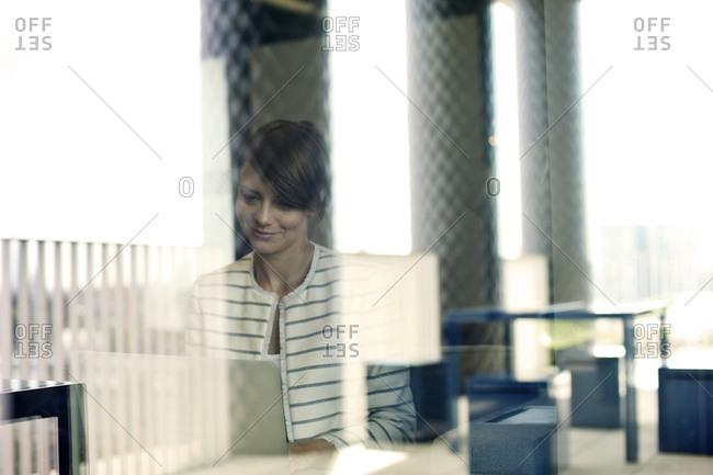 Businesswoman seen through window using laptop