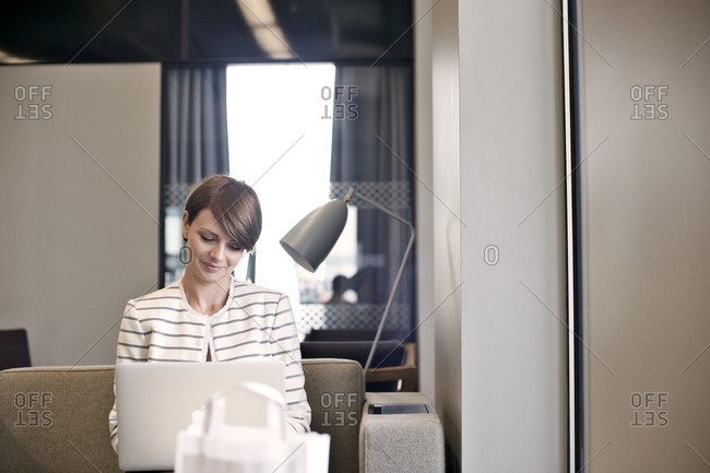 Businesswoman on couch using laptop