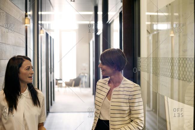 Two businesswoman talking in corridor