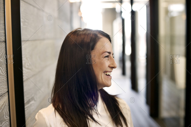 Businesswoman laughing in hallway