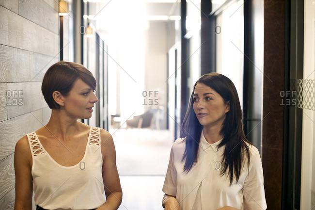 Two businesswoman talking in hallway