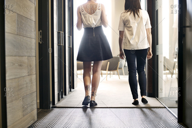 Two businesswomen walking in corridor