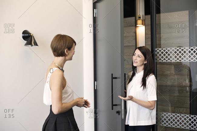 Businesswomen talking by door